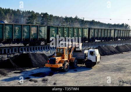 Pelle chargeuse charge le charbon en un camion-benne à la gare ferroviaire de fret Banque D'Images
