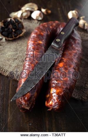 Chorizo espagnol avec couteau, sur planche de bois foncé Banque D'Images