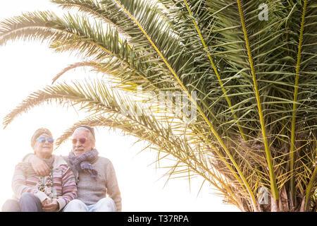 Heureux vieux portrait couple hug et rester dans l'amour ensemble dans le cadre d'un mode de vie à la retraite - palmiers tropicaux ciel clair blanc en arrière-plan - vêtements p Banque D'Images