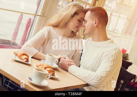 Jeune et belle femme assise près de l'un l'autre et gardant leurs mains ensemble tout en restant assis dans un café confortable. Couple d'offres romantique Banque D'Images
