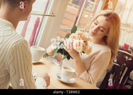 Attractive Woman holding bouquet de fleurs dans les mains et en souriant tout en célébrant l'anniversaire à vintage restaurant. Jeune couple ont dîner romantique au co Banque D'Images