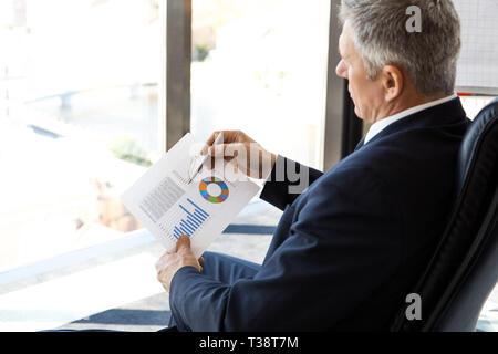 Mature businessman siégeant seul au pouvoir avec de grandes fenêtres panoramiques avec vue sur ville et à la recherche de schémas et rapports financiers Banque D'Images