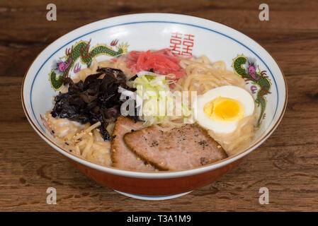 Tonkotsu Ramen au porc, lait de soja, bouillon de porc, les champignons noirs, les oeufs, les oignons, servi dans un bol en bois foncé, fond de table Banque D'Images
