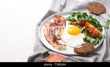 Photo de petit-déjeuner de style anglais à haute teneur en protéines avec des œufs, du bacon frit et roquette sur la plaque Banque D'Images