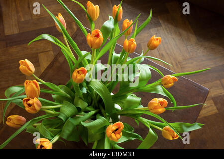 Passage tiré d'un bouquet de tulipes orange sur une table en bois rustique. Télévision jeter vue aérienne du style. Banque D'Images