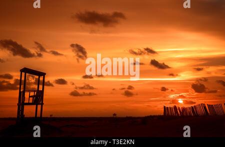Le soleil se couche derrière une barrière de sable et de secours sur l'extrémité ouest de Dauphin Island, Alabama. Banque D'Images