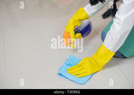 Femme Asiatique en salopette verte et jaune, des gants en caoutchouc de poussière un marbre - Image Banque D'Images