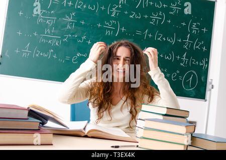 Jeune femme professeur de mathématique à l'avant du tableau Banque D'Images