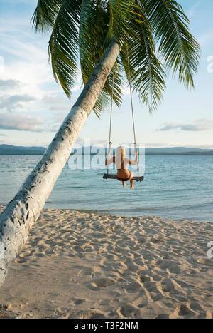 Vue arrière d'une femme dans une plage swing attaché à un palmier dans les îles San Blas. Destination de voyage, de vie / Maison de concept. Panama, Oct 2018 Banque D'Images