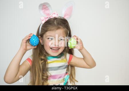 Cute little girl wearing Bunny Ears holding oeufs de Pâques peints et souriant. Banque D'Images
