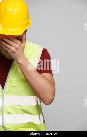 Photo de l'homme constructeur malheureux en casque jaune sur fond gris vide. Banque D'Images