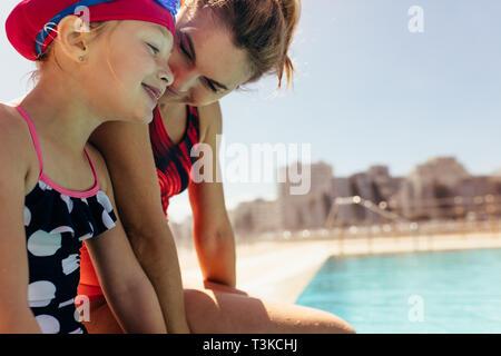 La mère et la fille assise à la périphérie de la piscine. Femme avec fille en maillot à la piscine. Banque D'Images
