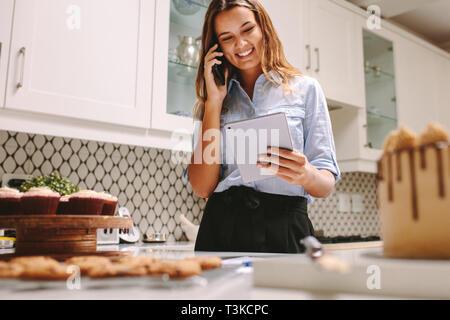 Jeune chef pâtissier prêt à démarrer sa propre entreprise la cuisson des gâteaux à l'ordre. Happy chef cuisiner dans une cuisine en souriant et à l'aide d'une tablette numérique et talkin