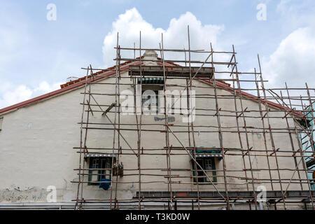 Maison en bois sur échafaudage, rénovation. Les échafaudages sur le bâtiment, mur et fenêtre. Système d'échafaudage en construction , Singapour . Site de construction, st Banque D'Images