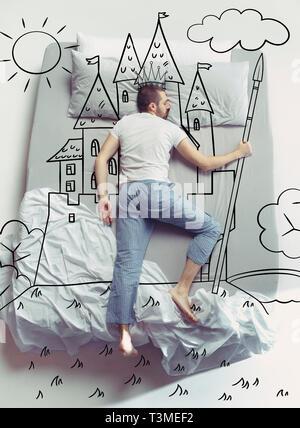Le roi de la famille. Haut Voir photo de jeune homme dormir dans un grand lit blanc à la maison. Rêves concept. À propos de rêve peint uni, château, couronne, soleil, paysage, pouvoir, contrôle, contes, monde pikestaff. Banque D'Images