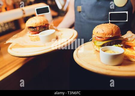 Les hamburgers et les frites sur le plateau en bois Banque D'Images