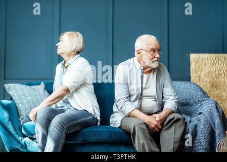 Senior offensé l'homme et la femme se sentir triste, assis de l'autre sur le canapé à la maison