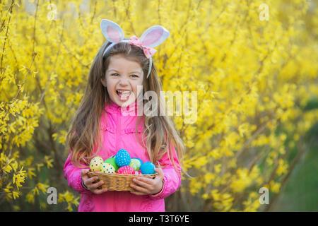 Cute little girl wearing Bunny Ears holding peint des oeufs de Pâques et des cris sur un fond de fleurs. Banque D'Images