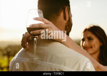 Gros plan d'une femme tenant un verre de vin rouge avec ses bras autour de son petit ami debout à l'extérieur. Vue arrière d'un homme debout avec sa petite amie