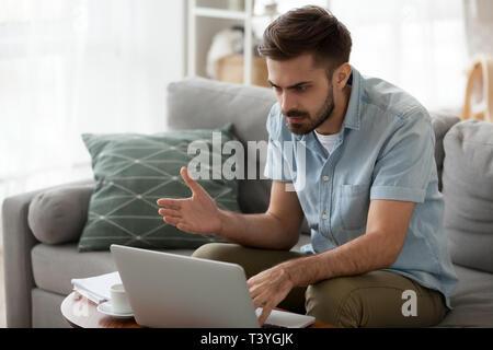 La lecture de l'homme en colère indignée des mauvaises nouvelles, des problèmes pour l'ordinateur portable Banque D'Images