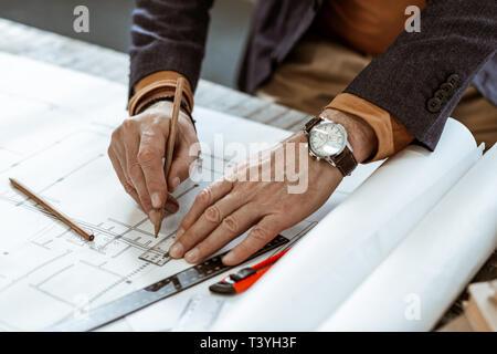 Les mains des hommes. Les mains de l'architecte d'intérieur de la main port watch travaillant sur des croquis Banque D'Images
