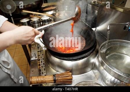 Chef, c'est en remuant les légumes avec de la sauce dans le wok à kirchen commerciale Banque D'Images