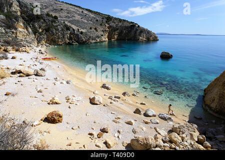 Jeune garçon marchant dans l'eau sur la plage, la mère couchée avec des kayaks en stationnement sur la rive, Croatie, Krk.