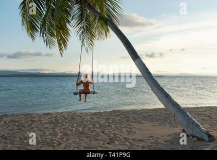 Vue arrière de la femme dans une plage swing attaché à un palmier dans les îles San Blas. RF Travel destination, mode de vie / Maison de concept. Panama, Oct 2018 Banque D'Images