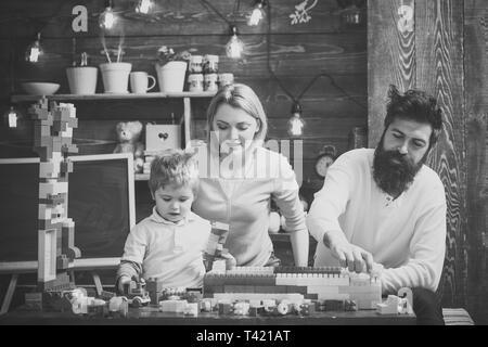 Famille heureuse de jouer avec à la maison. constructeur père aide à construire de mur de briques jouet. mère regardant fils jouer avec constructeur. Banque D'Images