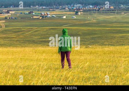 Fille de tourisme promenades dans l'herbe jaune sur le champ avec vue sur le village et les montagnes Banque D'Images