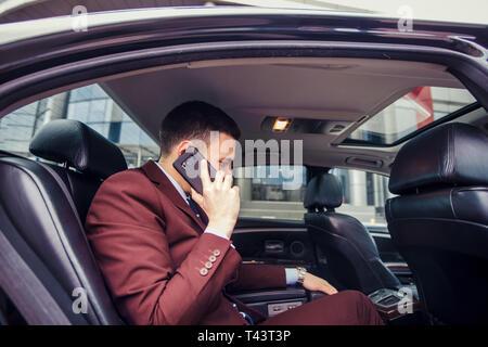 C'est Happy businessman talking on mobile pendant la conduite en voiture sa limousine Banque D'Images