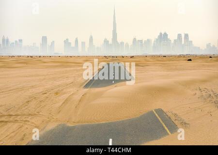 Vue de dessus, superbe vue aérienne d'une route déserte couverte par les dunes de sable au milieu de la Dubai Desert. Banque D'Images