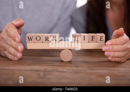 Close-up of Woman's Hand La protection du travail et de la vie des blocs de bois en équilibre sur Seesaw Banque D'Images