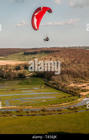 Seaford, East Sussex, Royaume-Uni. 13 avril 2019. Le vent froid de l'est amène les pilotes de parapente à High & Over dans les magnifiques South Downs surplombant la rivière Cuckmere. Banque D'Images