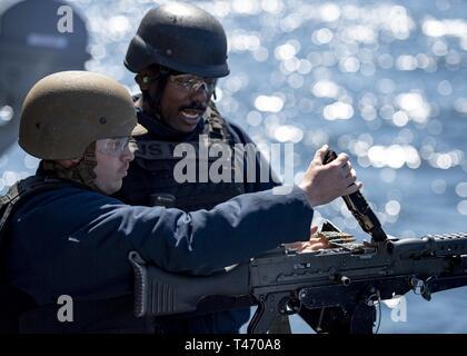 Océan (Mar. 13, 2019) maître d'Armes 1ère classe jeune Billy, droite, de Los Angeles, en Californie, indique à l'électronique d'aviation 2ème classe technicien Justin Sease, de Buckeye, Arizona), sur la manière de charger un M240B machine gun pendant un cours de qualification de l'incendie à bord des navires d'assaut amphibie USS Boxer (DG 4). Boxer est en cours la réalisation des opérations de routine dans le cadre d'un groupe amphibie USS Boxer (ARG) dans l'océan Pacifique. Banque D'Images