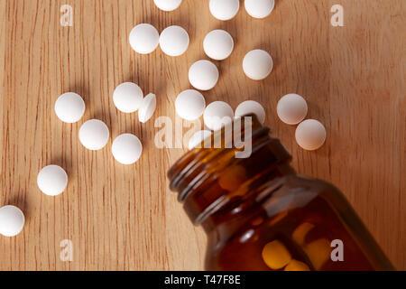 Le flacon en verre pour les médicaments. Les comprimés ronds blancs dispersés. Vue supérieure de la photo. Sur la table en bois. Banque D'Images