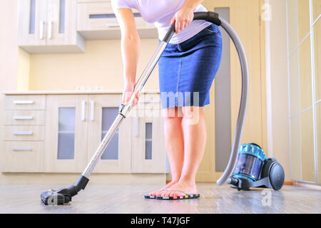 Une jeune femme est le nettoyage de l'appartement. Dans les mains d'un appareil électroménager, aspirateur. La notion de propreté et l'ordre dans les locaux Banque D'Images
