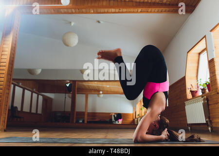 Jeune yogi attractive woman practicing yoga concept, debout dans salamba sirsasana exercice, wavecrest posent, de travail, le port des vêtements de sport, noir Banque D'Images