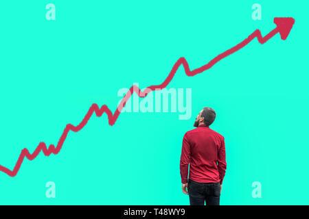 L'arrière du jeune homme beau barbu en chemise rouge et permanent à la recherche de plus en plus à l'analyse graphique graphique drawed diagramme sur l'espace de copie de bleu Banque D'Images
