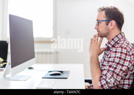 Stressed businessman assis à son ordinateur de bureau dans le bureau. Banque D'Images