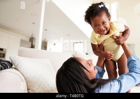 Bébé fille mère jouant avec son anneau de levage dans l'air à la maison Banque D'Images