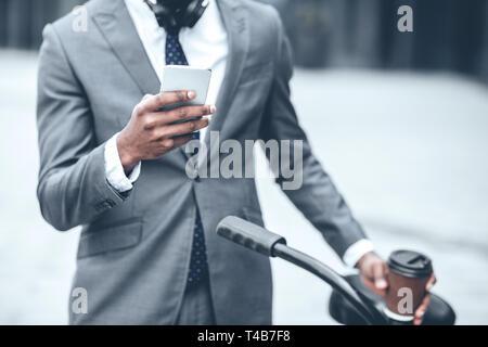 Businessman texting on phone se penchant sur le guidon Banque D'Images