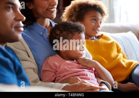 Close up d'enfants assis sur le canapé de leur salon regarder la TV avec leurs parents, side view Banque D'Images