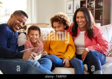 Séance jeune grands-parents avec leurs petits-enfants sur le canapé dans le salon eating popcorn et riant, vue de face, Close up Banque D'Images