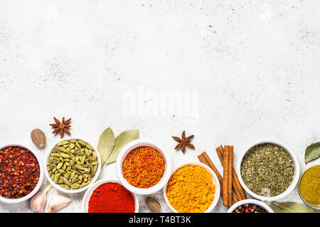 Ensemble d'épices sur la table en pierre blanche. Curry, curcuma, paprika, poivre, basilic, cannelle, cardamome et autres. Banque D'Images
