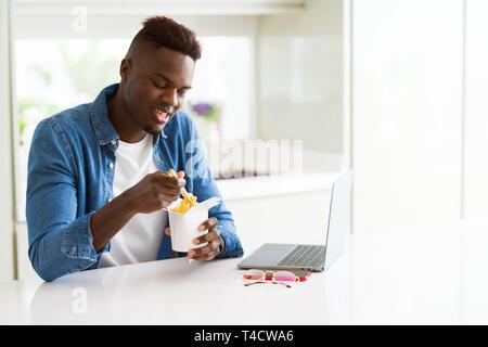 Beau jeune homme d'affaires de l'Afrique cuisine asiatique livraison manger et travailler à l'aide de concentré de l'ordinateur