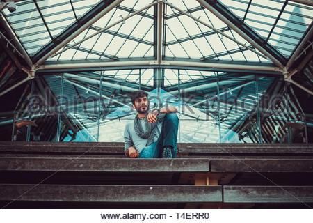 Homme portant un foulard gris assis sur l'escalier Banque D'Images