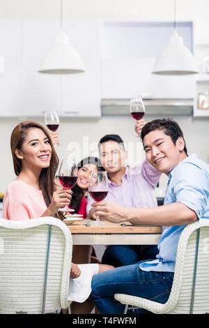 Jeune couple de prendre un verre avec des amis Banque D'Images
