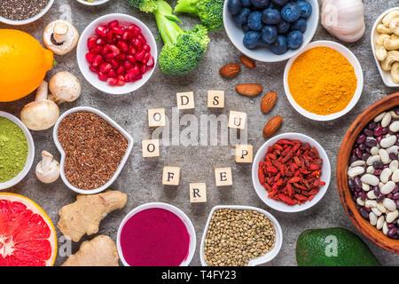 L'alimentation saine manger propre sélection: fruits, légumes, graines, noix, baies, superfood sur fond de béton. Vue de dessus avec copie espace nourriture vegan. Banque D'Images