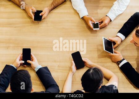 À partir de la récolte au-dessus des hommes et femmes d'affaires officielles assis en cercle au tableau et l'utilisation de téléphones mobiles dans office Banque D'Images
